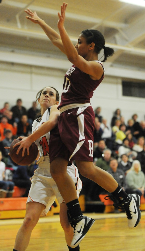 Brewer's Lindsay Houp, left, gets jammed by Bangor's Danae Johnson as she attempts a lay up at Brewer on Monday.