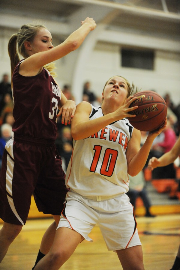 Bangor's Sarah Bragg swipes at the ball as Brewer's Alexa Grindle attempts a shot during first half action on Monday at Brewer.