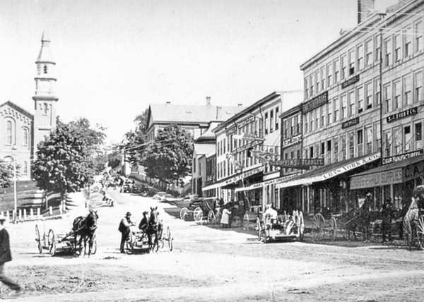 "This 1884 view up Park Street at East Market Square shows the area known as ""Undertakers Row"" because of the many undertakers and coffin dealers there. Abel Hunt's store, side by side with his former partner Enoch Tebbetts, can be seen. The park to the left is where Bangor's City Hall now stands."