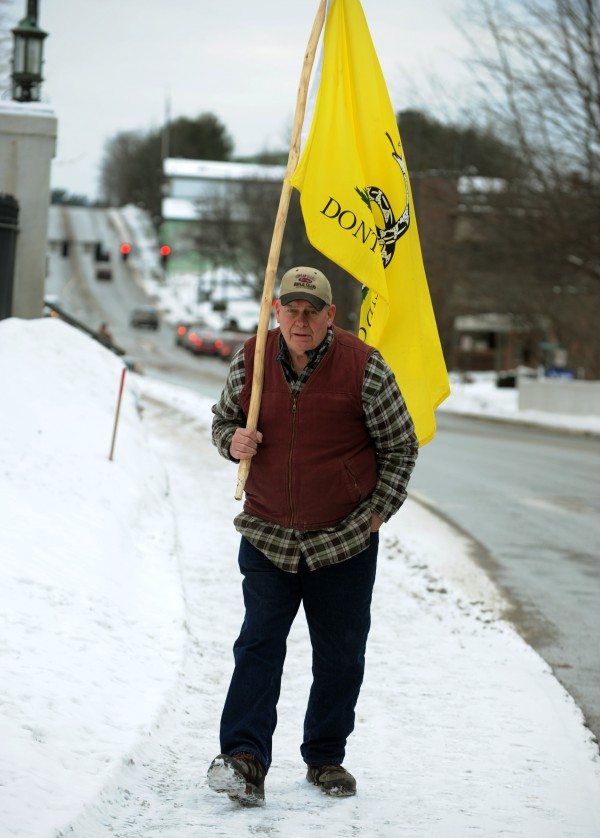 A man carrying a &quotDon't tread on me&quot flag joins Second Amendment protesters gathered near the capitol building in Augusta on Saturday.