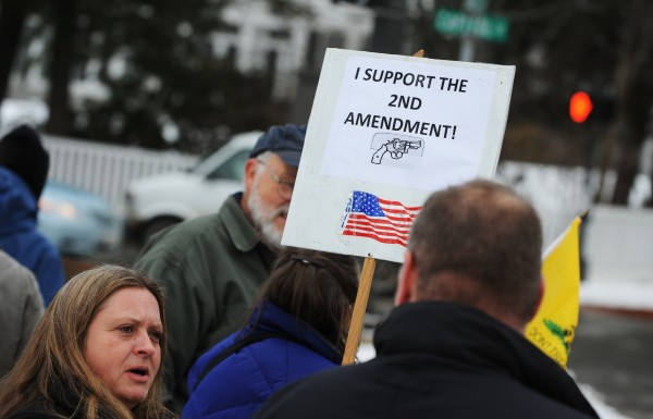 Martha Alward carries a sign while protesting for the Second Amendment near the Capitol building in Augusta on Saturday.
