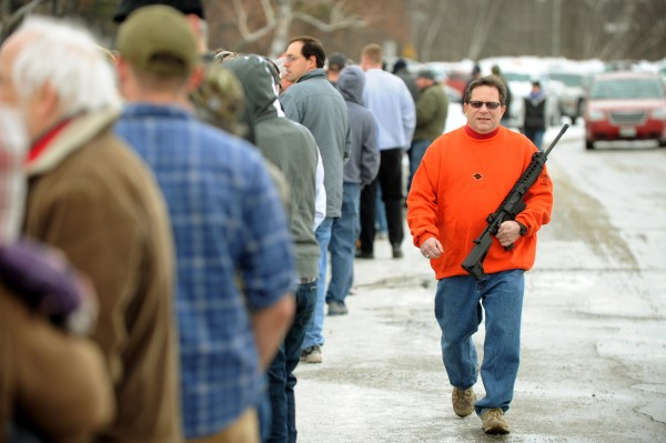 A man carries an assault-style rifle along a line of several hundred people as they wait to enter a gun show at the Augusta Civic Center in Augusta on Saturday.