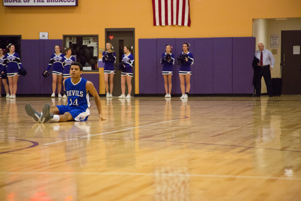 Lewiston's Abdi Hussein checks the score after being knocked to the ground against Hampden on Friday.