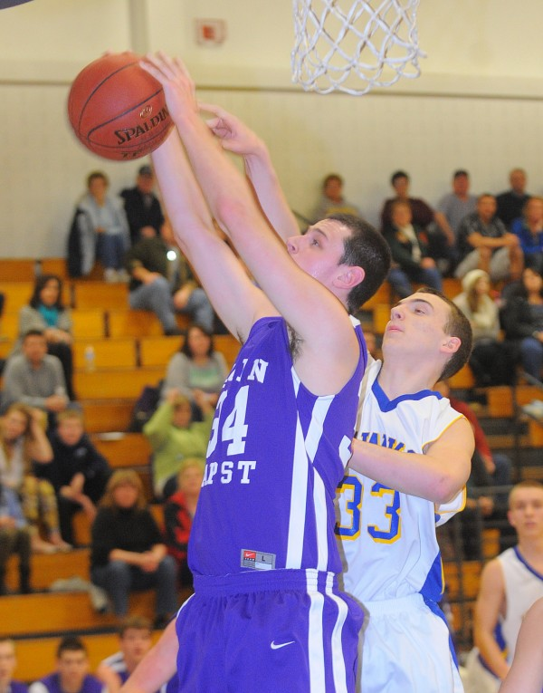 John Bapst High School's Andrew Gatchell (left) takes a rebound over Hermon High School Ryan Kelley during the game in Hermon Tuesday.