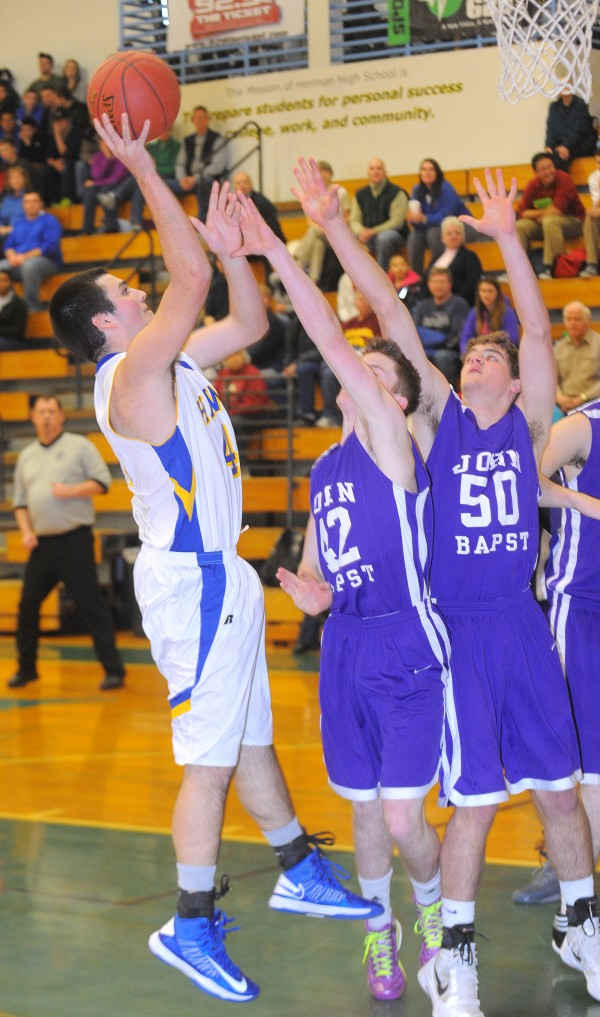 Hermon High School's Joey Martin (left) tries to make a shot over John Bapst High School's Adam Strang (right) and Riley Tapley during the game in Hermon Tuesday.