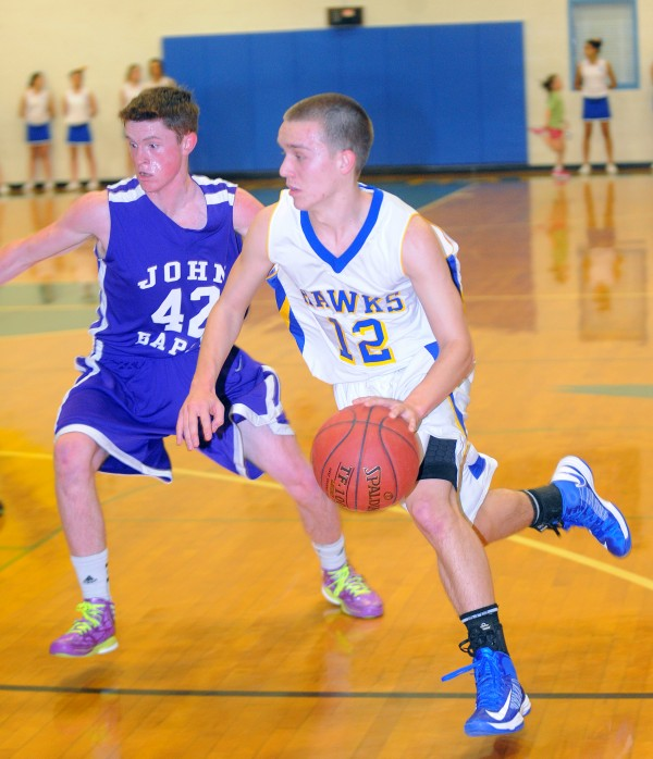 Hermon High School's Jacob Rioux (right) drives past John Bapst High School's Riley Tapley during the game in Hermon Tuesday.