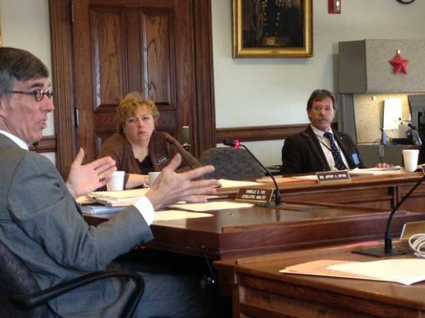 Gerry Reid, at left, the director of the Maine Bureau of Alcoholic Beverages and Lottery Operations, gestures during a hearing before the Legislature's Legal and Veterans Affairs Committtee Monday. Reid was explaining details of a plan to rebid a contract for the state's wholesale liquor business. He said Monday that Maine was losing about $30 million a year in alcohol sales to New Hampshire.