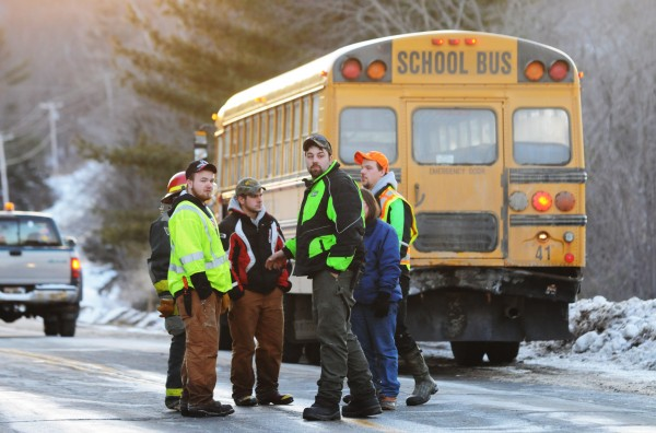 Members of the Dixmont Fire Department congregate in the road near a school bus that was involved in a collision on Monday on Route 9/202 near box 1185 on Monday.