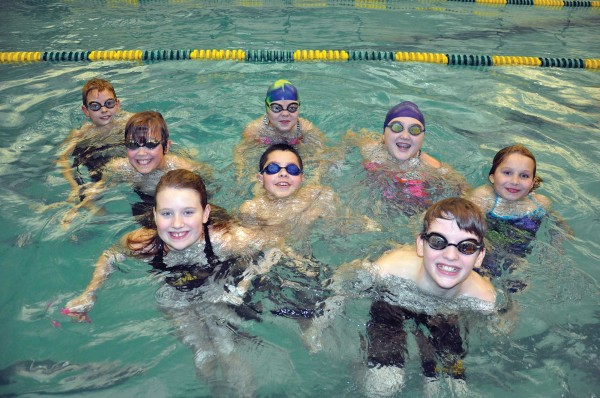 5th grade members of the MDI YMCA Sharks swim team encourage all adults to swim laps in their annual aquathon to support the team.
