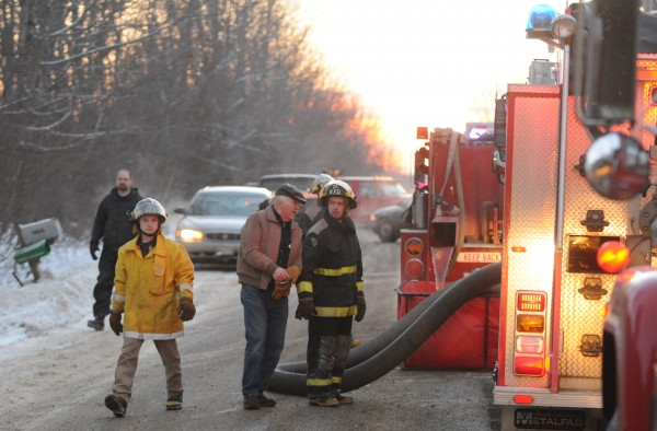 Winterport Fire Department personnel man fire fighting equipment at 165 Monroe Road in Monroe on Sunday during a garage fire.