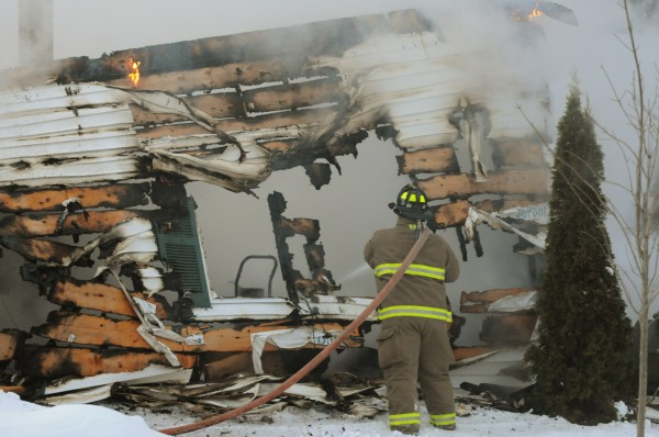 A fireman hoses down what is left of a garage at 165 Monroe Road in Monroe on Sunday. No one was hurt or killed in the fire according to Winterport Fire Department officials.