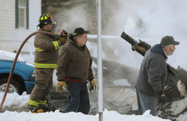 Spectators a get a closer look a garge fire at 165 Monroe Road in Monroe on Sunday.
