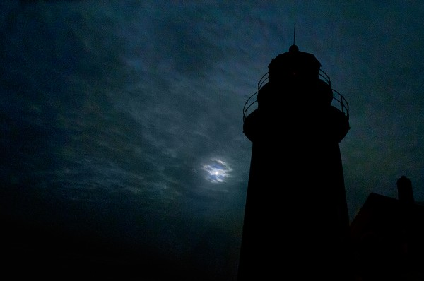 West Quoddy Head Lighthouse silhouetted in an eerie and moody moonlight image.