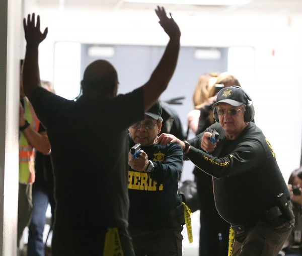 Armed Maricopa County Sheriff posse members draw their weapons on a suspect during a simulated school shooting in Fountain Hills, Ariz., on Saturday.