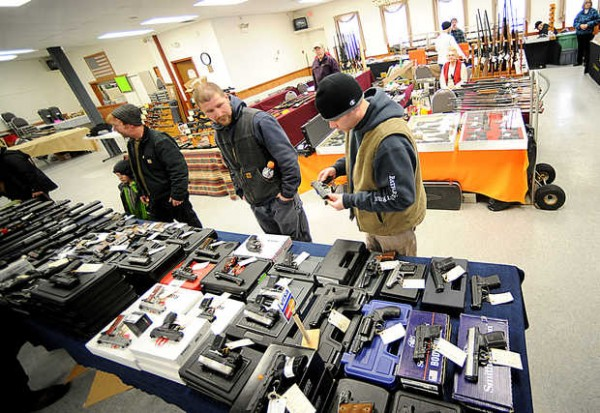 Luke Dalton, right, his brother, Doug, second from right, his father Ronald, and Doug's son, Wyatt, 5, check out handguns at JT Reid's Annual Gun Show in Lewiston on Saturday. The snow kept shoppers away, but organizer John Reid hoped Sunday would bring in more people.