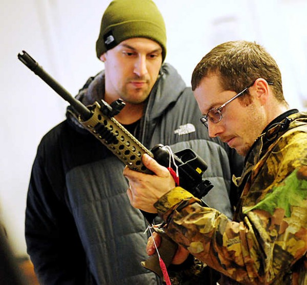 Daniel Keough, right, and Charles Derosby inspect a gun at JT Reid's Annual gun show in Lewiston on Saturday.