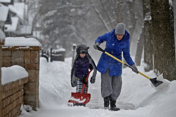 Amy Wolf gets help from her daughter Audrey Wolf, 6, with shoveling the early snowfall on Friday in Minneapolis, Minnesota.