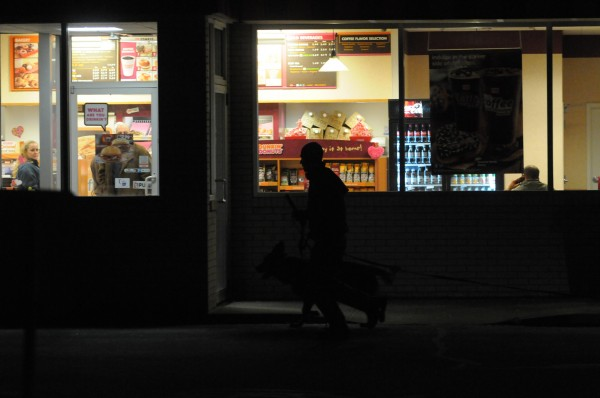 A Bangor Police officer with a K-9 runs past the front entrance of Dunkin' Donuts on Broadway in Bangor on Tuesday night, Feb. 5, 2013. Sgt. Rob Angelo said police are investigating a robbery were a person approached the drive-thru window and demanded money.