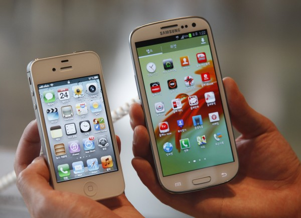 An employee holds Apple's iPhone 4s (L) and Samsung's Galaxy S III at a store in Seoul in this file photo from Aug. 24, 2012.