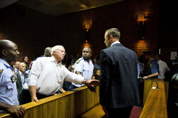 South African &quotBlade Runner&quot Oscar Pistorius (right) talks to his father, Henke, after his court appearance in Pretoria, South Africa, on Friday.