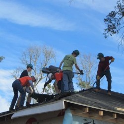 "Falmouth students and members of the ""Tiger Team,"" a group of retired men who work with Habitat for Humanity on a regular basis, strip shingles to prepare for replacing the roof on David McCulloch's Mississippi home."