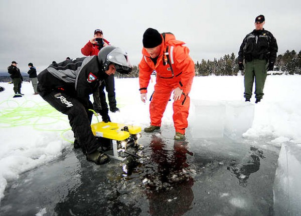 Maine Warden Bruce Loring (right) looks on as Chris Roy (left) and Mike Joy remove a remotely operated vehicle from Rangeley Lake for members of the media Wednesday as they made a final attempt to recover the bodies of missing snowmobilers Glen Henderson, Kenneth Henderson and John Spencer before spring.