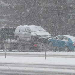 Tow trucks pick up cars crashed along Interstate 295 southbound Friday morning after a multicar pileup reported during the morning commute. A major storm had begun in southern Maine, forecast to bring more than a foot of snow by the time it completes Saturday.