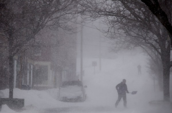 A person shovels snow on Columbia Street in downtown Bangor during a winter storm that hit Bangor early Saturday morning, bringing strong winds and mounds of snow.