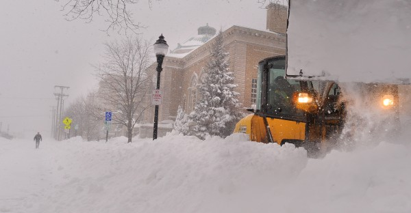 A front-end loader clears the snow from the sidewalk in the front of the Bangor Public Library on Saturday.