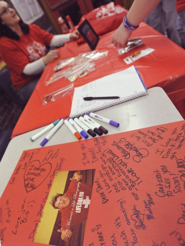 Well-wishers sign a card for Dexter High School cheerleader David McKusick after he suffered a heart valve infection last year.
