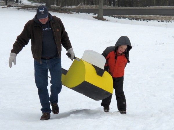 Rob Hudson helps Grayson Mote, 7, carry his homemade cardboard sled up the hill at Woodlawn Museum in Ellsworth after its inaugural run during Ellsworth's Winter Carnival on Saturday, Feb. 16, 2013.