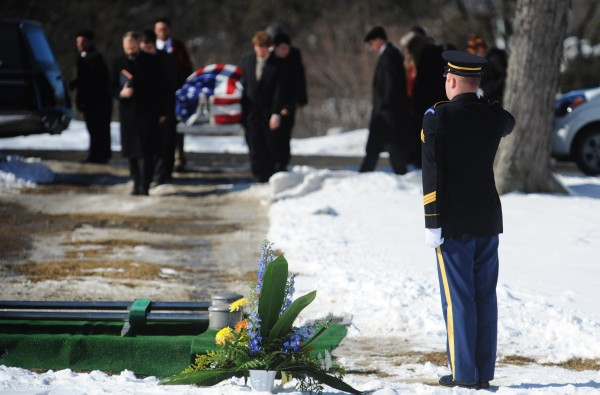 Sgt. Michael Quint, a member of the  Maine Army Guard's Maine Military Funeral Honors Program, stands at attention as the casket is taken off a hearse at Mount Pleasant Cemetery on Monday for the program's 9000th veteran's funeral since 2003.