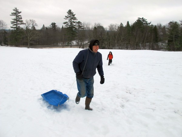 Jeff Wright, Ellsworth's ice rink director, trudges back up the hill after racing Grayson Mote, 7, in background, down the hill at Woodlawn Museum during Ellsworth's Winter Carnival on Feb. 16, 2013.