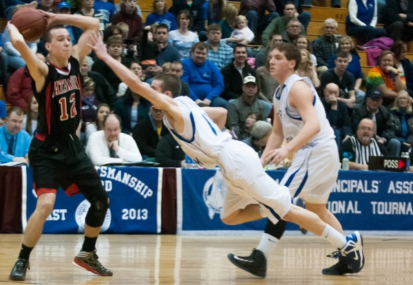 Central Aroostook's Chandler Brewer (center) dives at Katahdin's William Livezey (left) at the Bangor Auditorium on Monday, Feb. 18, 2013.