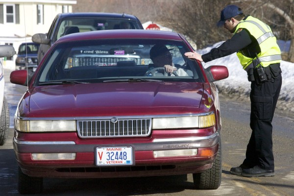 Brewer police Officer Thom Tardiff turns around traffic on Day Road in Brewer after a portable propane tank exploded in the back of a truck at 125 Day Road on Wednesday morning, causing major damage to the vehicle.