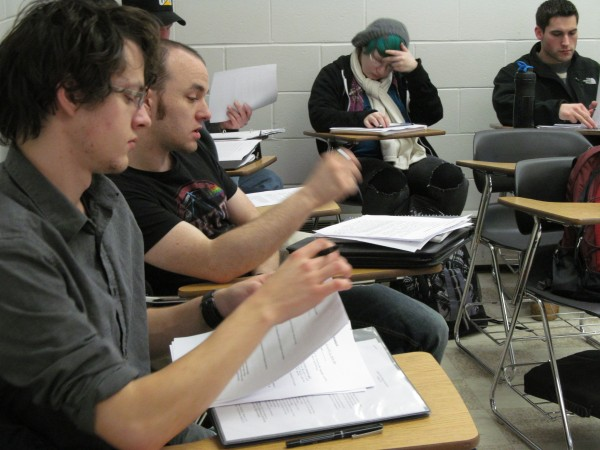 Patrick Howard (left), 21, flips through writing he plans to share during a discussion in a Wednesday morning class at Southern Maine Community College's South Portland campus. The school's new slate of 7 a.m. classes have proven popular, community college officials have said.