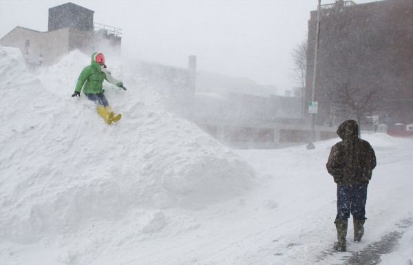 Christina Hurd (left) and Cory Wells play on a snow bank on Columbia Street in downtown Bangor.