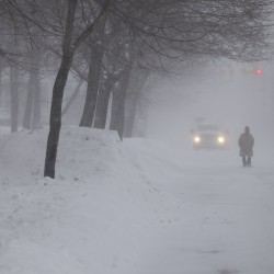 A man walks down Third Street in Bangor during a winter storm that hit the city early Saturday morning and continued throughout the day.