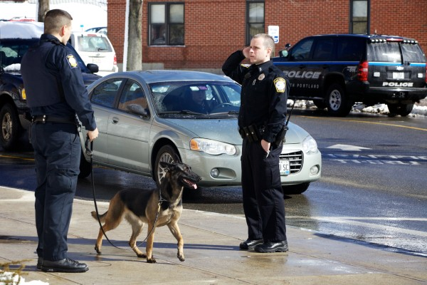 A Portland Police officer and his South Portland counterpart use a dog to search buildings at Southern Maine Community College in South Portland on Monday morning after the college received multiple bomb threats.