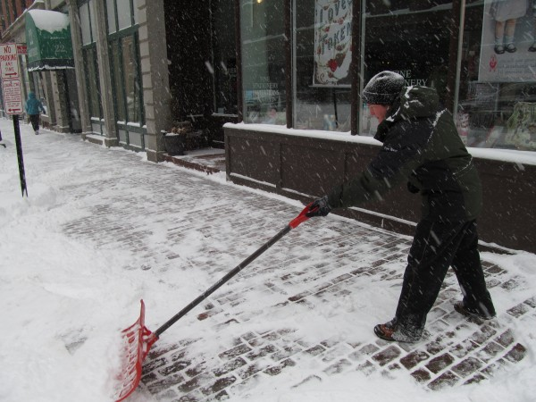 Stacie Burton clears the sidewalks around Papier Gourmet on Free Street in Portland Friday morning, Feb. 8, 2013. Burton works for property management firm Fore River Co. and said she plans to clear snow around the whole block before she's finished.