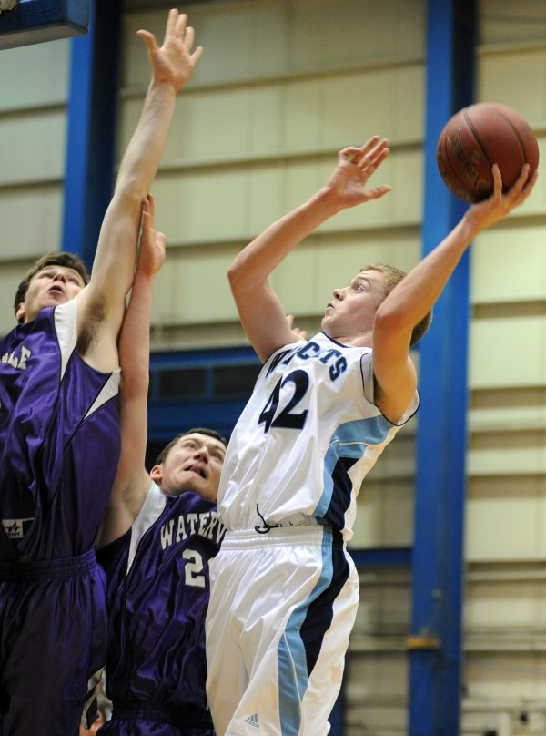 Presque Isle's Tyler Brooks goes up for a shot over Waterville defenders John-Peter Michaud (left) and Josh Gormley (center) in first half action of the boys Class B quarterfinal game at the Bangor Auditorium Saturday morning.