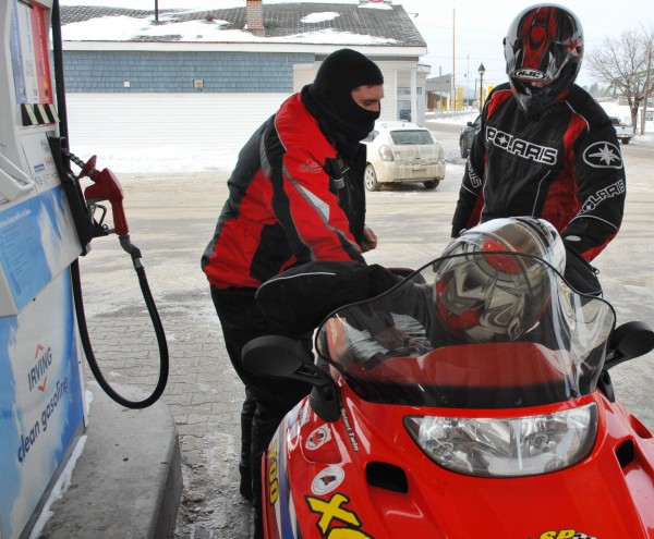 St. John Valley Sledders Andrew Sullivan (left) and Jason Lizotte fuel up before a planned 200-mile trip around Aroostook County Saturday morning, Jan. 26, 2013. Snowmobilers are hoping an impending storm will drop enough snow for them to hit the trails.