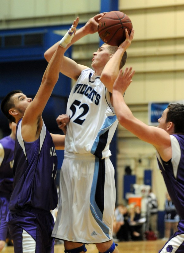 Presque Isle's Bradley F. Shields goes up for a shot over Waterville defenders Christopher Hale (left) and Josh Gormley in first half action of the boys Class B quarterfinal game at the Bangor Auditorium Saturday morning.