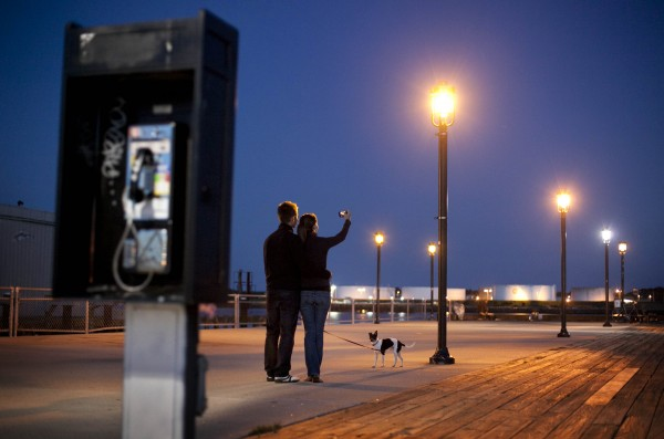 A couple photographs themselves at dusk on the Maine State Pier.