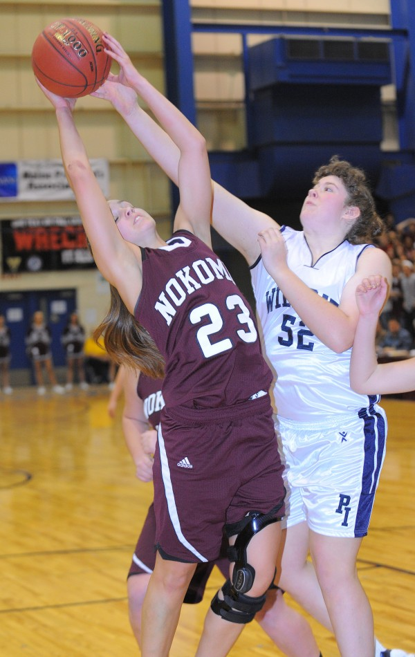 Nokomis' Kelsie Richards (left) takes a rebound over Presque Isle's Egan Nelson during the first half of the Eastern Maine Class B championship game in Bangor on Saturday, Feb. 23, 2013.