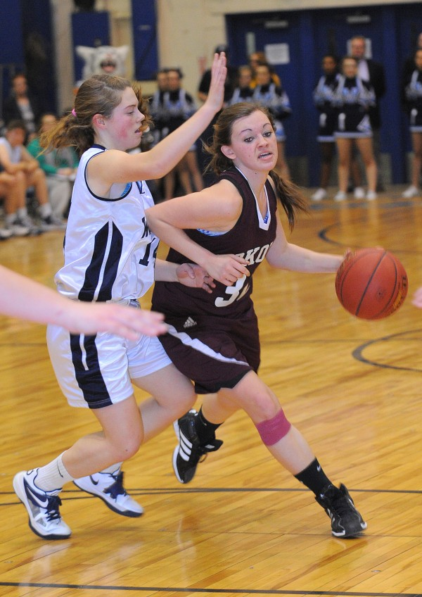 Nokomis' Taylor Shaw (right) drives past Presque Isle's Chandler Guerrette during the second half of the Eastern Maine Class B championship game in Bangor on Saturday, Feb. 23, 2013.