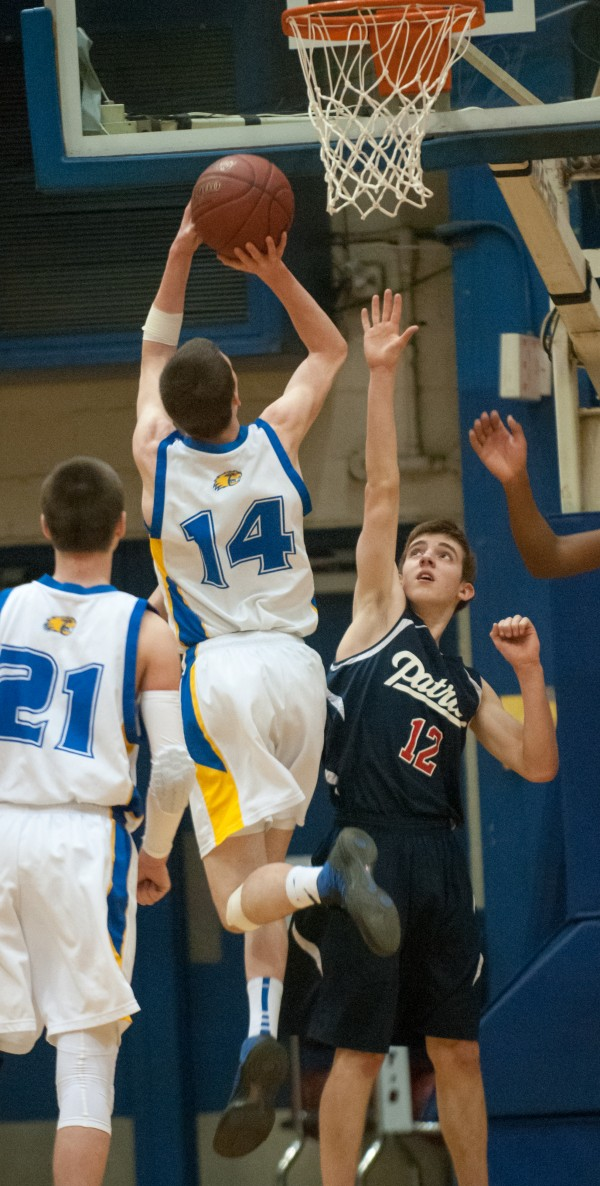 Washburn's Mitchell Worcester (center) drives to the hoop against Bangor Christian's Seth Pearson (right) at the Bangor Auditorium on Monday, Feb. 18, 2013.