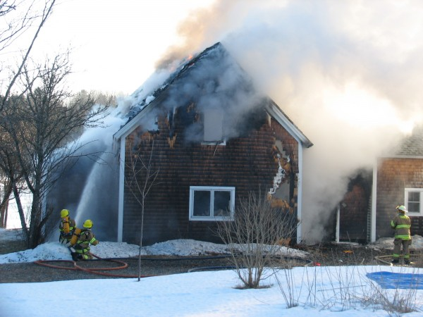 Firefighters try to extinguish a morning blaze at a home off Route 3 in Trenton on Tuesday, Jan. 29, 2013. The house was significant'y damaged in the fire.