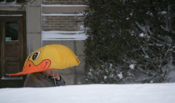 A man smokes a cigarette on Harlow Street in Bangor on Saturday during the snow storm.