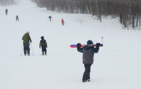 A boy carries his skis behind his head as he walks along the base of the hill at Big Squaw Mountain Ski Resort on Big Moose Mountain on Sunday, Feb. 17, 2013. The mountain hosted the third week of its Mogul Mites learn-to-ski program.